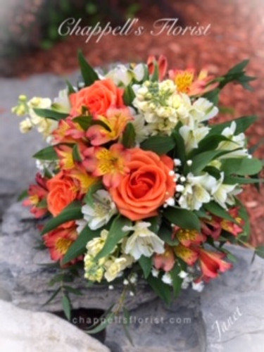 Beautiful hand tied wedding bouquet in shades of orange, soft yellow and whites.