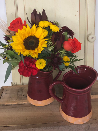 Beautiful fall in Vermont ceramic pitcher designed in autumn tones. Nice assortment of orange roses, safari sunset, sunflowers, variety of foliage.