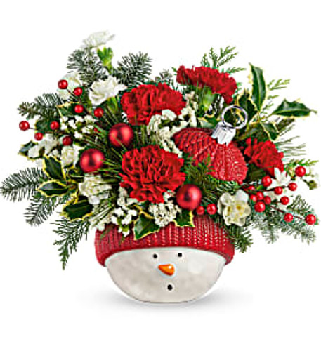 Red carnations, miniature red carnations,  variegated holly are accented with noble fir, flat cedar, and white pine. Delivered in Teleflora's Snowman