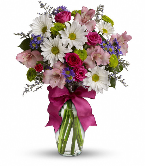 A mix of fresh flowers such as spray roses, daisy and button spray chrysanthemums, Monte Cassino asters and limonium, in shades of white, pink, green, purple and lavender. Delivered in a vase adorned with a matching ribbon.