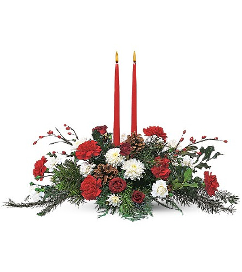 Long and Low centerpiece with two taper candles. Designed with Vermont winter greens, Red Carnations, White mums, Natural Pine Cones. Delivered locally by Chappell's Florist