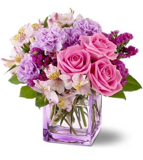 Pink roses and alstroemeria, raspberry sinuata statice and lavender carnations are delivered in a beautiful glass vase.