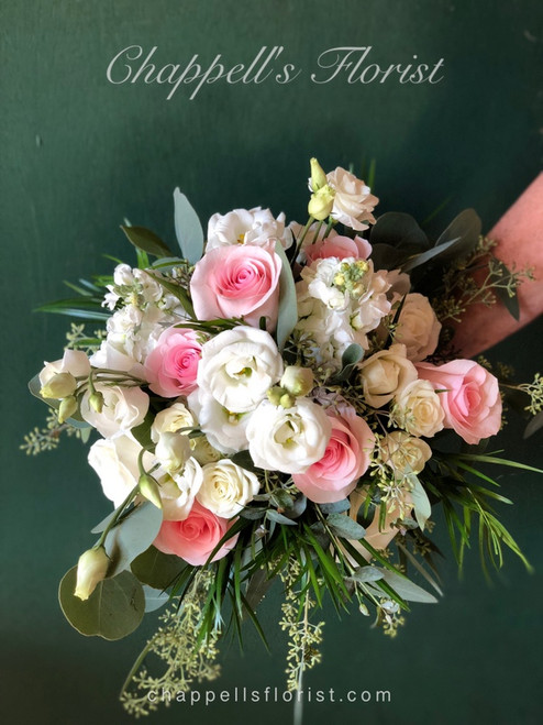 Beautiful soft cascade of novia pink rose, white lisianthus, assorted greenery, white spray roses.