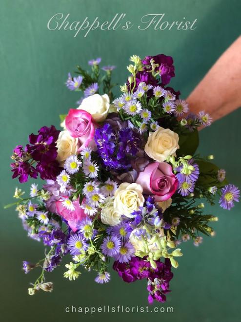 Hand Picked Beautiful. Shades of Purple that include stock, larkspur, rose, novi belgi, asters, alstromaria.