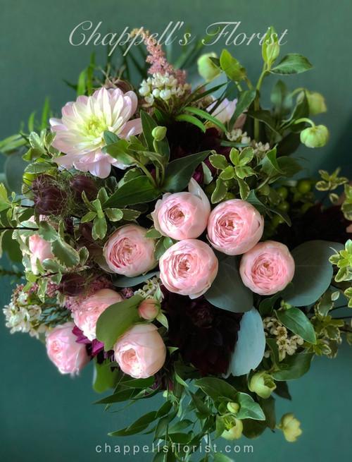Everything you want. California pink spray rose, pink and burgandy dahlias, hellebore, silver dollar eucalyptus, mini micro pitt, and mixed foliage.