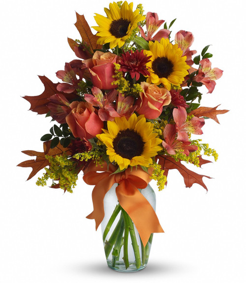 The cheerful arrangement includes orange bi-color roses, yellow sunflowers, dark orange alstroemeria and rust cushion spray chrysanthemums accented with orange ribbon and assorted greenery.
