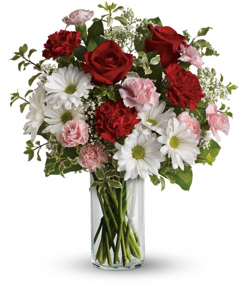 The fragrant bouquet includes white Asiatic lilies and red roses accented with fresh greenery delivered in a classic clear glass vase.