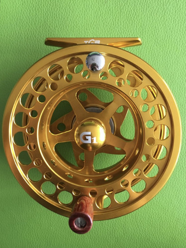 Gold Fly Reel.  3 bearings, 2 in the spindle, 1 in the hand carved wooden handle.