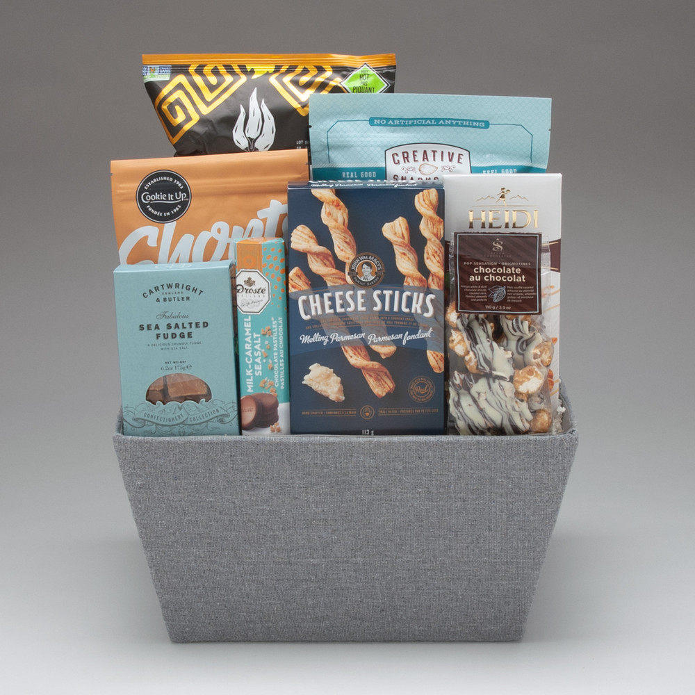 With an untraditional and altogether lovely colour palette this basket comes loaded with a bounty of snacks and treats, all easily opened & shared. We love the Cheese Sticks, the amazing Sea Salted Fudge, and the excellent handmade cookies from Cookie It Up (Canadian)! This basket is ideal for an office group or family to share, and will certainly bring some oohs and ahhs!!