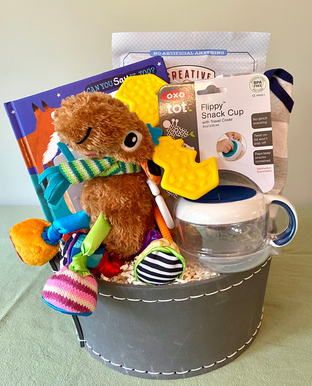 This altogether fun baby gift holds some practical gear for baby, and features the Mortimor Moose Educational Toy by Lamaze with bright colours and a variety of textures for baby to explore. And we think Mom & Dad will appreciate the yummy treats we've tucked in for them!