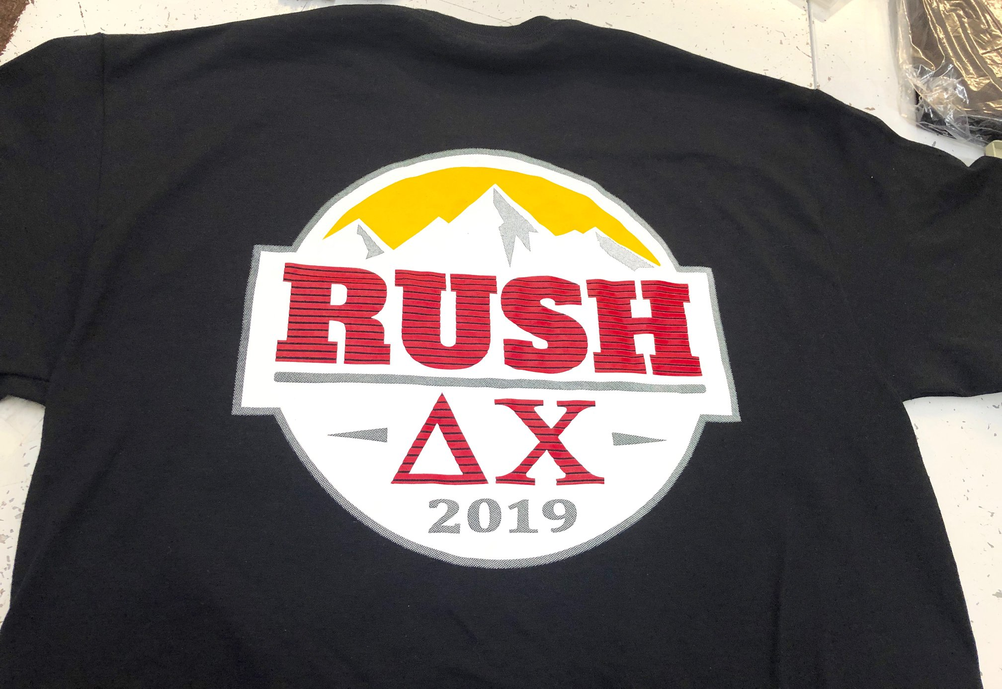 Multi colored delta chi fraternity screen print on a black t-shirt