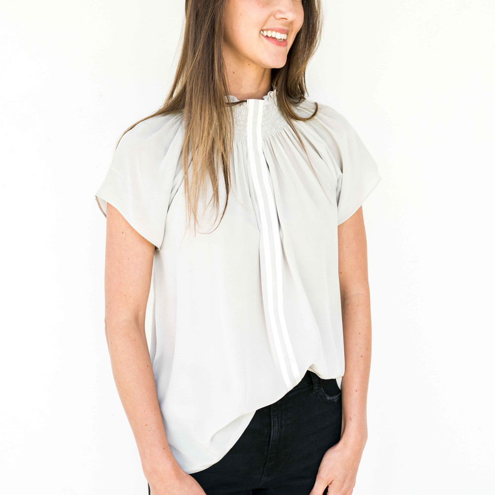 Light Grey Crepe/Ivory  This elevated staple with its sporty contrast stripe is already a customer favorite! Pair this season's gorgeous new colorways with everything from white jeans, a blazer tor an open cardigan. The blouse can also be worn off the shoulder for a stunning evening look. We recommend sizing down in this style.