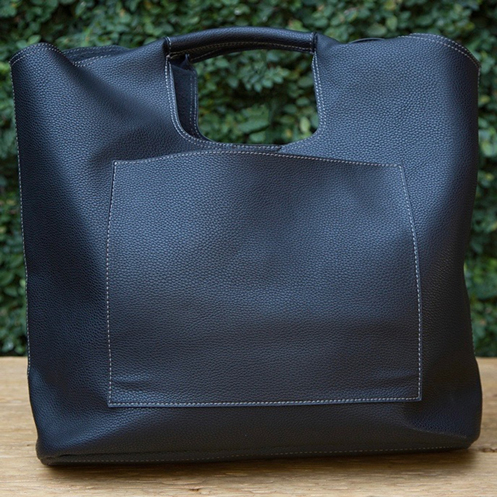 Vegan leather tote with double handles and magnetic snap closure. Includes outer slip pocket, inner zip pocket, and inner slip pocket.