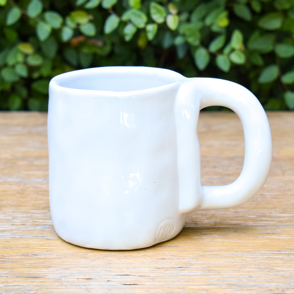 The interesting, classic ceramic mug you've been searching for. This handmade mug has just enough of an organic feel to elevate your coffee experience. The classic white ceramic gives it a clean, modern look and together all of these designs create a perfect mug.