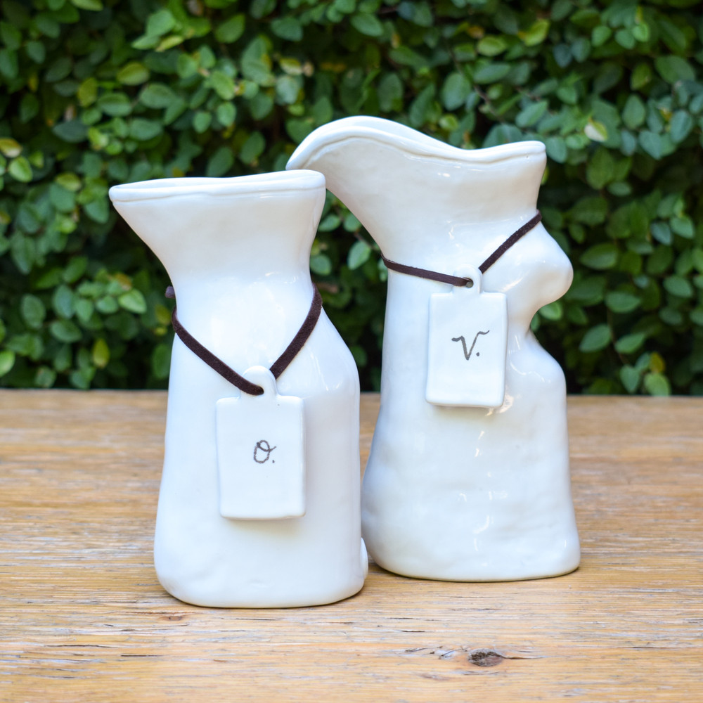 The perfect finishing touch to your place setting! This coordinating white ceramic oil and vinegar set will sit lovely with any style table and keep your essentials at your fingertips! Each cruet has a ceramic tag secured by a leather tie.