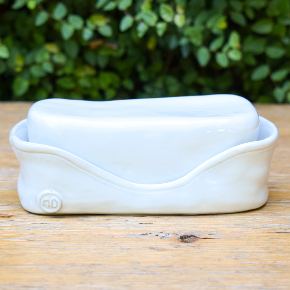 The perfect butter dish for any table, wether you store in the fridge of the counter this is your serving piece! The white ceramic bottom securely holds one stick of butter and the top sits perfectly atop to give you a covered and protected butter dish you can use for everyday and special occasions.