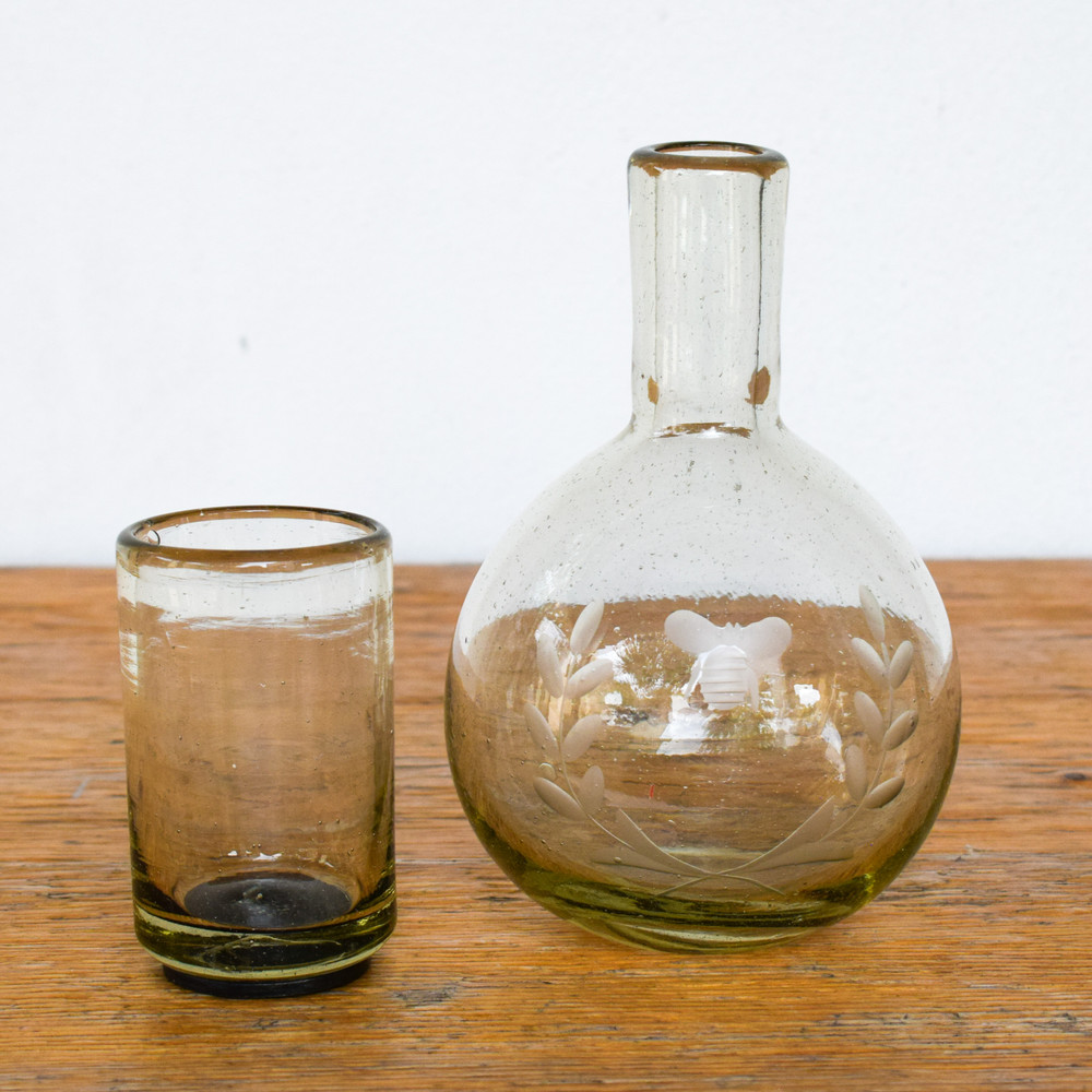 Mouth blown clear glass carafe with wee-bee engraving and iron footed drinking glass with gift box.