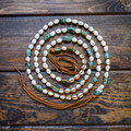Tess Jewelry fresh water pearl necklaces hand wrapped in suede can be worn as a stacked choker, tied as a bolo or a combination of both.  Extremely comfortable, unique and stylish!  This handmade piece includes turquoise pieces alongside the beautiful pearls.