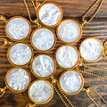 """The perfect amount of sophistication and classic design combined with your sun sign. These 1.25"""" mother of pearl Zodiac Pendants offer the right amount of understated glam. They are surrounded by a gold vermeil casing, and come on a beaded chain.     1.25"""" diameter   Sold with beaded chain  MOP and 14k vermeil"""