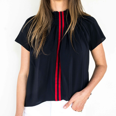Navy/Red  This elevated staple with its sporty contrast stripe is already a customer favorite! Pair this season's gorgeous new colorways with everything from white jeans, a blazer tor an open cardigan. The blouse can also be worn off the shoulder for a stunning evening look. We recommend sizing down in this style.