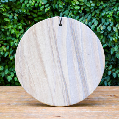 These serving pieces feature predominantly tan-colored sandstone with graphic, narrow mineral banding that highlights a variety of colors from red to lavender to gray. No two pieces are alike. The serving board has a leather strap, and all pieces are waxed to protect the stone from oils.
