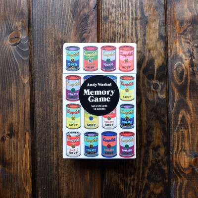 """Exercise your brain by testing your memory with this soup can memory game. Cards depict authentic colors of Andy Warhol's iconic soup can art.   Size: 4.75 x 7.5 x 2.25"""" - Card Size: 7.25 x 3.375"""" - 20 cards, 10 matches"""
