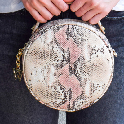 A favorite from our Austin designer Kelly Wynne... this handbag will be a crowd favorite with timeless snakeskin and a unique round, comfortable design.