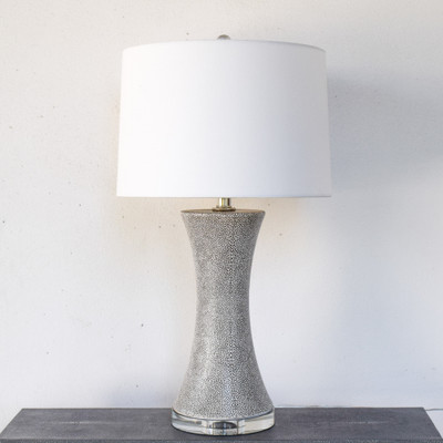 The Sacha lamp is simple, modern, and classic all in one. The highlights of the shagreen pattern shines through giving depth to the texture, which is perfectly complimented by the crystal base. The Sacha lamp is sure to bring warmth and style to any room.