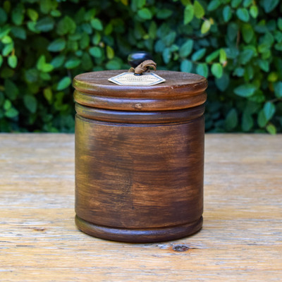 A hand-poured soy wax candle sits tightly in the round wooden box complete with an accompanying lid.