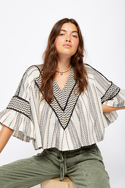 A light and easy top perfect for any party! The Free People Runnin On A Dream Top features striped embroidery throughout , an exaggerated ruffle sleeve with a boxy cropped silhouette.