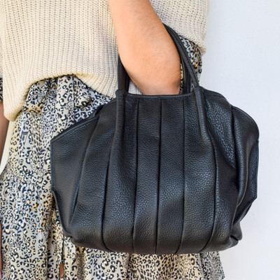 The bag that will hold everything! The Zoe tote's oversize look it the best balance of catch-all and look chic doing it. The added detail on the front gives depth to the black patent while maintaining a sleek look.