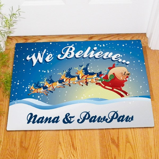 """Personalized Christmas doormat featuring Santa in his sleigh and proclaiming """"We Believe""""."""