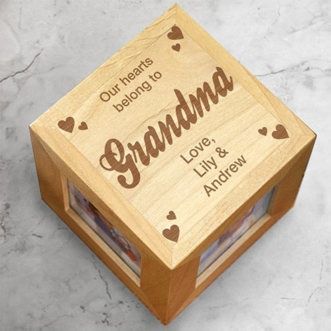 "Natural wood photo cube says ""Our Heart Belongs To Grandma"" and can be personalized with as many as eight names."