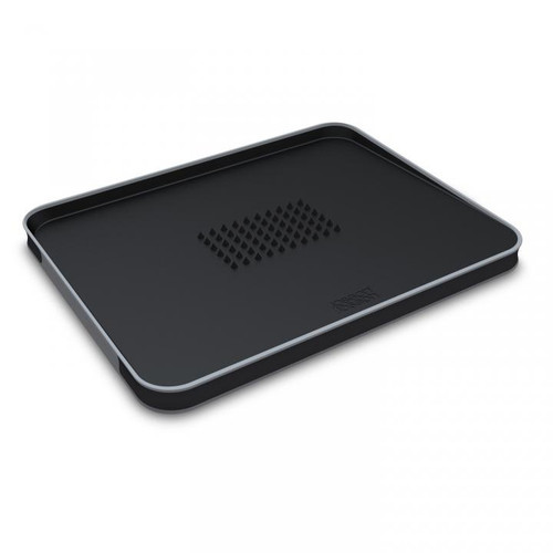 Black, rectangular, sloping carving board with contrasting grey lip. In the middle is a rectangular array of conical points to provide grip.