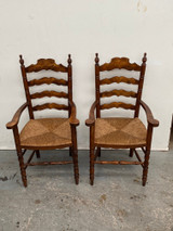 A pair of French oak ladder back carver chairs