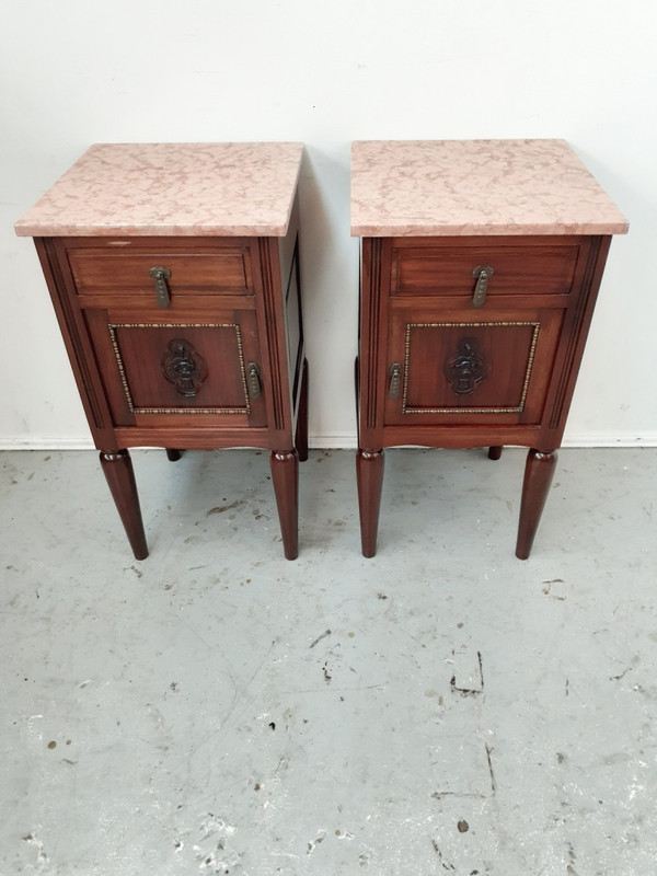 A French mahogany matching pair of marble top bedside tables