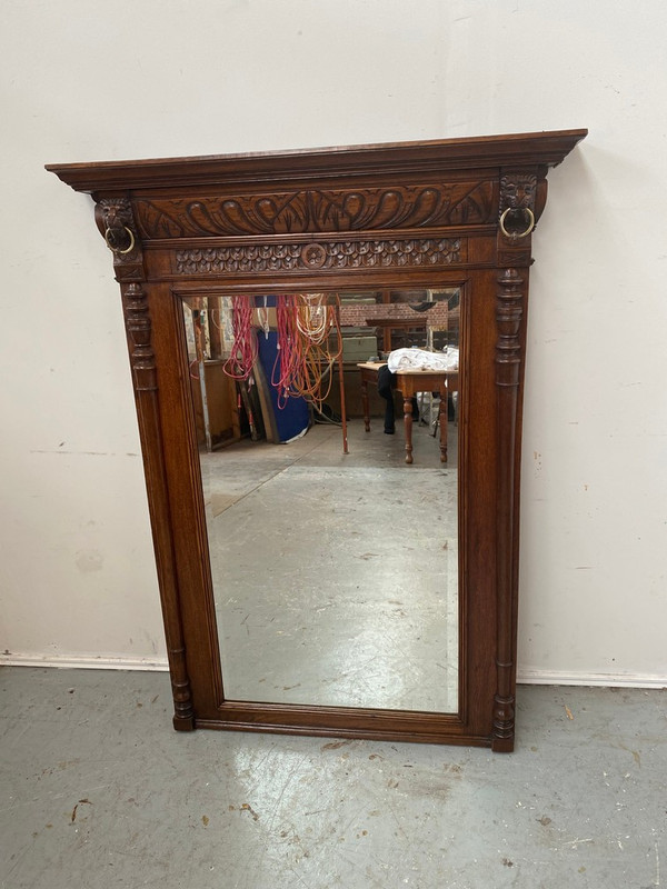 French oak beveled mirror with lion head carvings