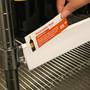 Employee adding a wine shelf talker to Metro wire shelving label holder.