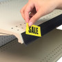 Person inserting sale tag into self-adhesive info strip.