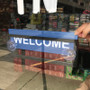 Person inserting welcome sign into suction cup sign holder.