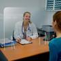plastic personal portable sneeze guard on a doctors office reception desk