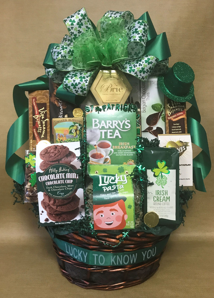 """A large St. Patrick's Day themed basket, all decorated with a St Patrick's Day bow and enhancements. It is chock full of goodies for sharing. Includes coffee, tea, cookies, chocolates, cheese, crackers, chips, pretzels and more. Includes a free ribbon banner that says """"I'm Lucky To Know You! Great corporate client gift, thank you gift, raffle prize or party basket. Items of equal or greater value may be substituted depending on availability."""