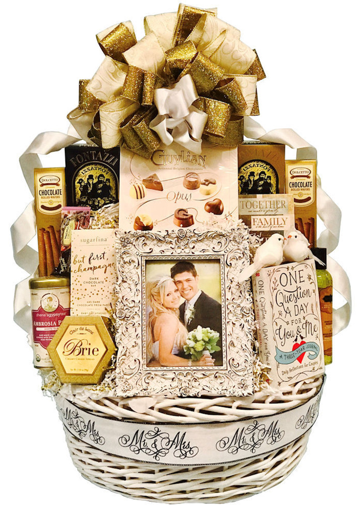 """A stunning presentation and memory making assortment for the newlyweds! Includes a fancy, designer wedding frame, A book they will write together and cherish forever called """"One Question A Day"""", a candle, massage lotion, cheese, crackers, tea, cookies, gourmet sweet and savory pretzels, fine chocolate assortment,  a champagne chocolate bar, and two doves as an enhancement in a white basket.  Items of equal or greater value may be substituted depending on availability."""