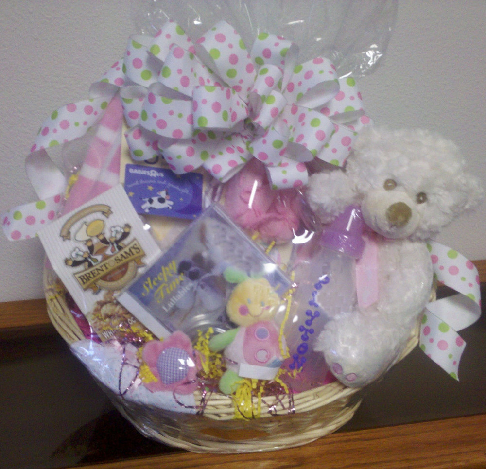 Adorable baby girl basket with an assortment of gift items for the baby. Includes a plush bear, baby booties, baby frame, bib, baby music CD, personalized baby bottle, and cookies, chocolate and  tea for mom and dad to share.