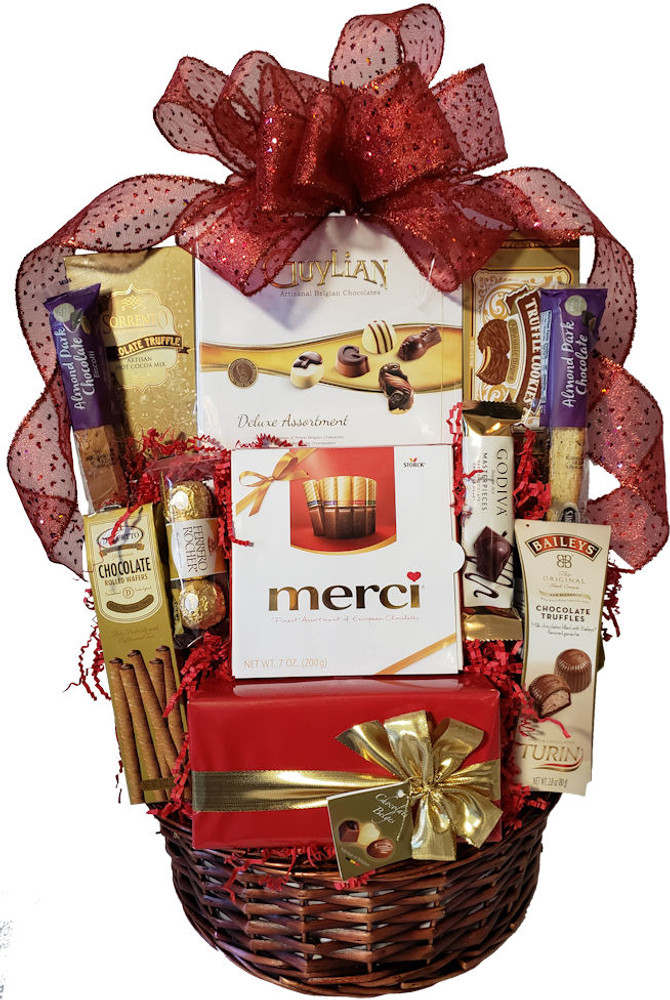"""This amazing basket will thrill any chocolate lover!  It includes assorted boxes  of fine European truffles, Belgian truffles, and assorted chocolates.  assorted cookies, and more.   This makes a great birthday, thank you or Valentine's Day gift for any serious chocoholic. It is also great for a Valentine's Day promotion to clients (for the whole office to share) with a free ribbon banner that reads """"We Love Your Business!  Items of equal or greater value may be substituted depending on availability and the discovery of great new seasonal items."""