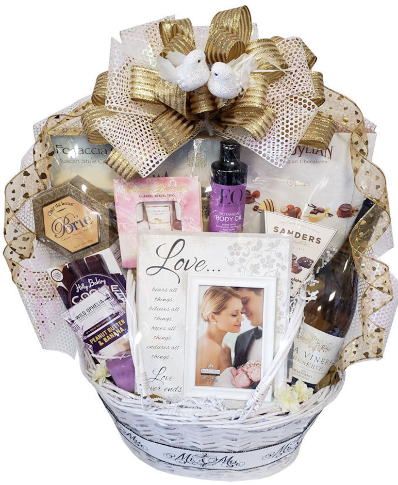The new Mr. and Mrs. will start their new lives together with romantic memories that will last a lifetime. the gift includes:  An elegant drop handle basket (makes a great picnic basket later) Brie Cheese Focaccia Crisps (crackers) Fine Belgian Chocolates Gourmet Cookies Chocolate Sea Salt Caramels A scented candle Massage Oil Mini Spa Kit A beautiful designer frame to capture the memory Sparkling cider (see note below to upgrade to wine)  *To upgrade to red wine, white wine, or champagne, or to customize the gift in any way, please give us a call.  Items of equal or greater value may be substituted depending on availability and the discovery of great new seasonal items.