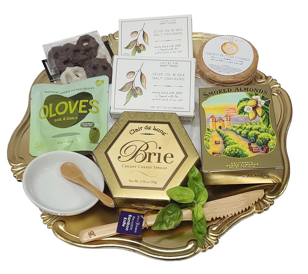 A beautiful scalloped gold tray topped with appetizers for two. Includes; Olive Oil and Sea Salt Crackers Brie Bamboo Knife Olives Porcelain Olive Dish Mini Bamboo Olive Spoon Smoked Almonds Chocolate Cookies Items of equal or greater value may be substituted depending on availability