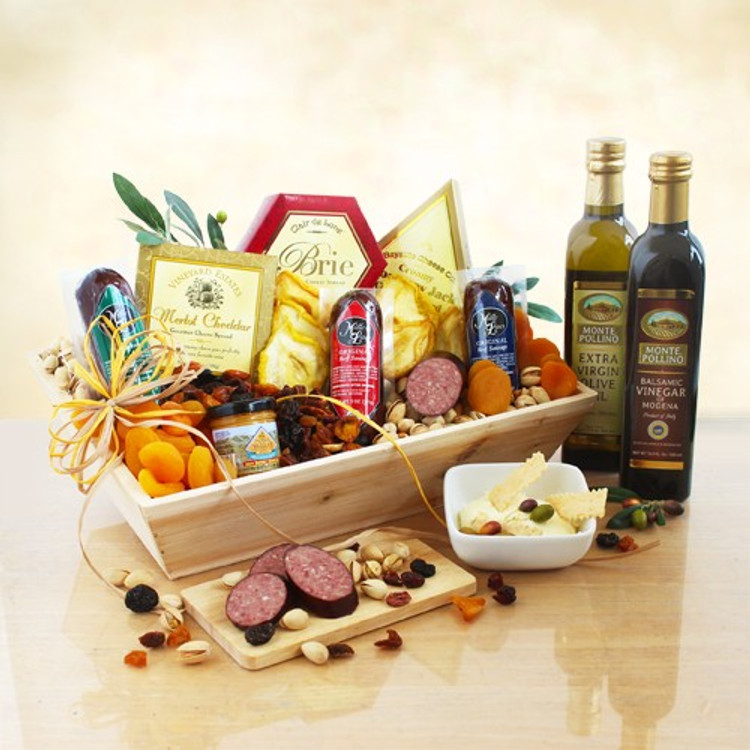 A large assortment of cheeses, sausages, crackers, olive oil, vinegar and much more presented in a wood crate.