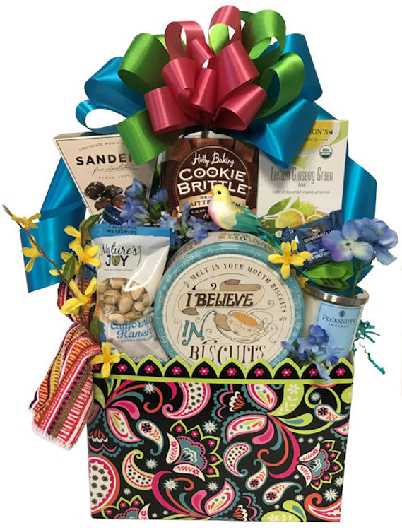 A colorful and festive gift box is overflowing with biscuits, gourmet cookies, chocolates, tea, pistachios, and gourmet wafers. Also includes a decorative kitchen towel and scented candle. This is a great gift for a relaxing get together with a friend or two.
