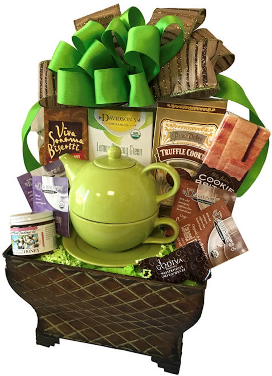 A beautiful metal planter filled with tea, biscotti, cookies, honey, and a tea for One teapot with cup and saucer.